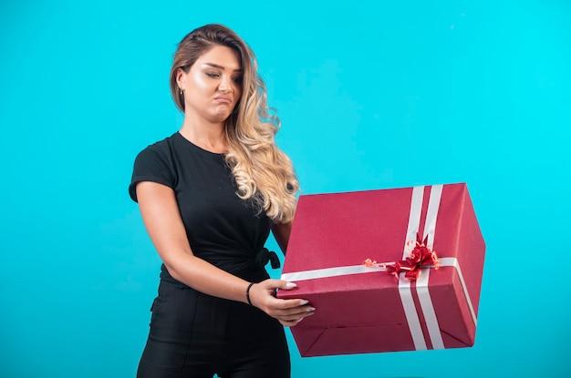 Jeune fille en chemise noire tenant une grande boîte-cadeau et semble confus.