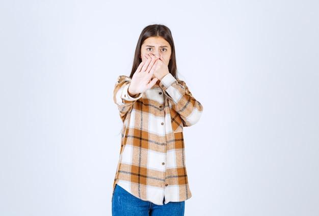 Jeune fille en chemise rayée disant stop sur blanc.