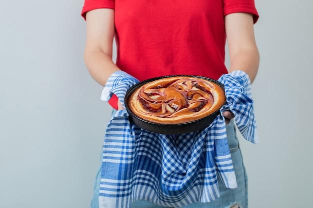 Jeune fille en chemise rouge tenant une tarte dans une poêle noire