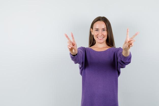 Jeune fille en chemise violette montrant le signe de la victoire et à la joyeuse vue de face.