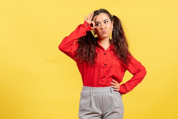 Jeune fille en chemisier rouge posant sur jaune