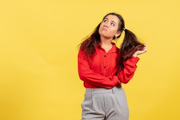 Jeune fille en chemisier rouge posant avec visage ennuyé sur jaune