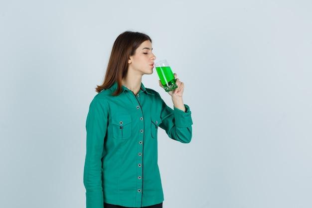 Jeune fille en chemisier vert, pantalon noir buvant un verre de liquide vert et regardant focalisé, vue de face.