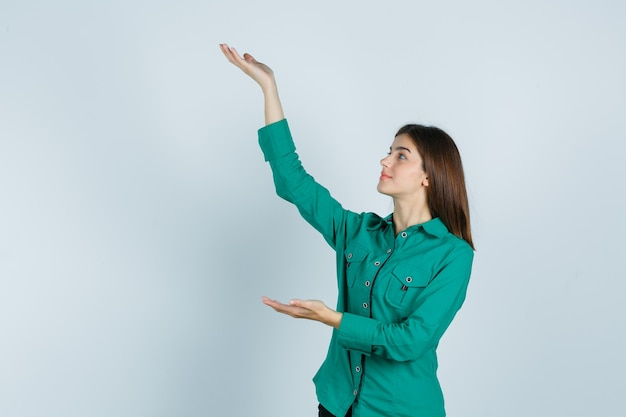 Jeune fille en chemisier vert, pantalon noir étirant les mains comme tenant quelque chose et à la joyeuse, vue de face.