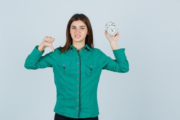 Jeune fille en chemisier vert, pantalon noir montrant le pouce vers le bas, tenant une horloge et regardant harcelé, vue de face.