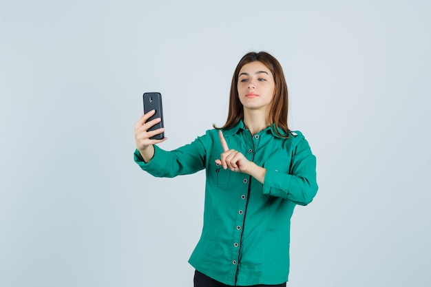 Jeune fille en chemisier vert, pantalon noir montrant tenir sur un geste minute tout en faisant un appel vidéo et à la jolie vue de face.