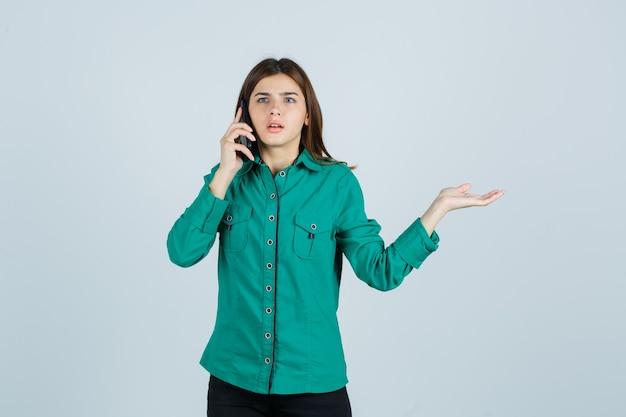 Jeune fille en chemisier vert, pantalon noir parlant au téléphone, étalant la paume de côté et à la surprise, vue de face.