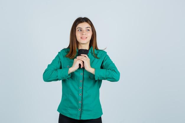 Jeune fille en chemisier vert, pantalon noir tenant le téléphone à deux mains et regardant heureux, vue de face.