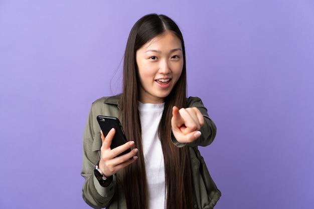 Jeune fille chinoise à l'aide de téléphone mobile isolé
