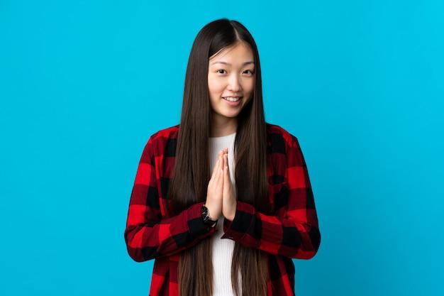 Jeune fille chinoise sur bleu isolé maintient la paume ensemble. la personne demande quelque chose