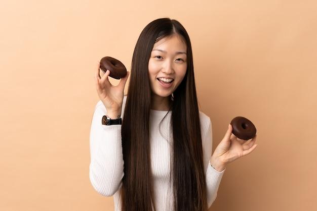Jeune fille chinoise sur fond isolé tenant des beignets avec une expression heureuse