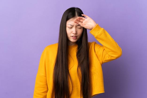 Jeune fille chinoise sur fond violet isolé avec une expression fatiguée et malade