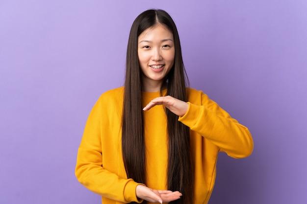 Jeune fille chinoise sur fond violet isolé tenant un espace de copie imaginaire sur la paume pour insérer une annonce