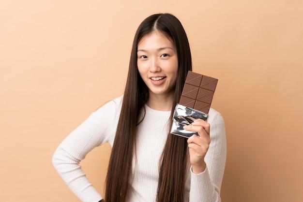 Jeune fille chinoise sur isolé prenant une tablette de chocolat et heureux