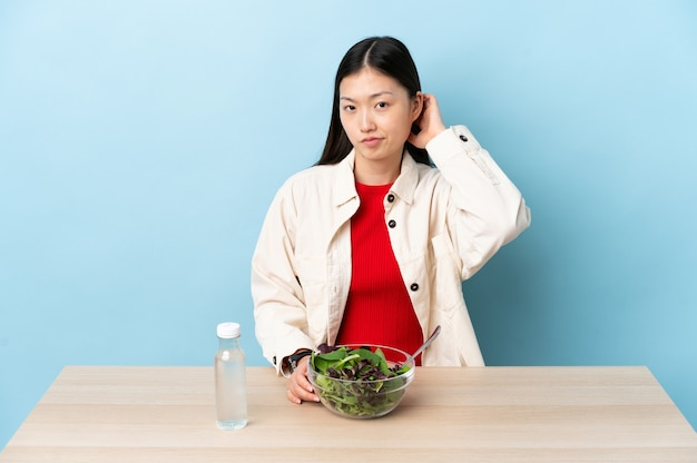 Jeune fille chinoise mangeant une salade ayant des doutes
