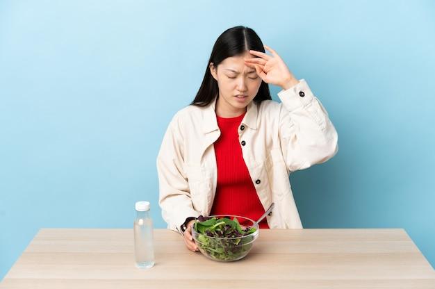 Jeune fille chinoise mangeant une salade avec une expression fatiguée et malade