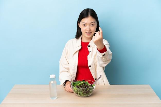 Jeune fille chinoise mangeant une salade faisant le geste à venir