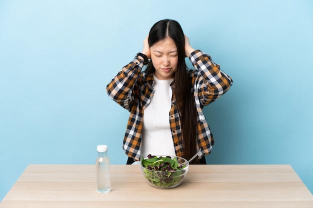 Jeune fille chinoise mangeant une salade frustrée et couvrant les oreilles