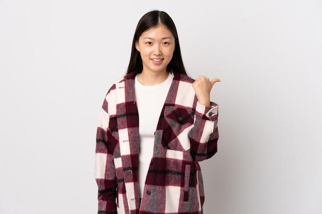 Jeune fille chinoise sur un mur blanc isolé pointant vers le côté pour présenter un produit