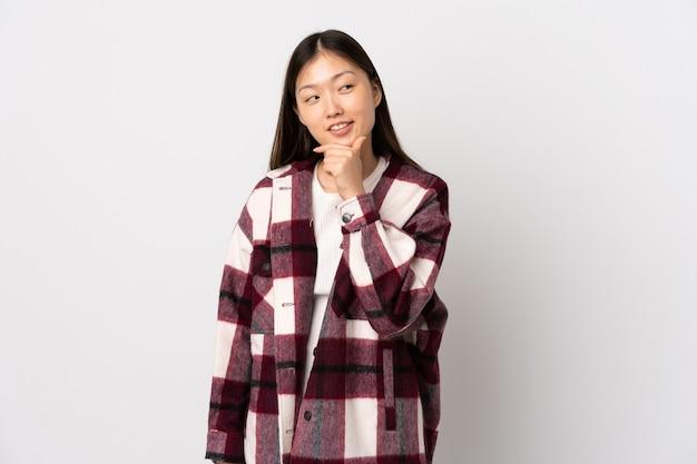 Jeune fille chinoise sur un mur blanc isolé à la recherche sur le côté et souriant
