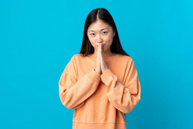 Jeune fille chinoise sur un mur bleu isolé maintient la paume ensemble. la personne demande quelque chose