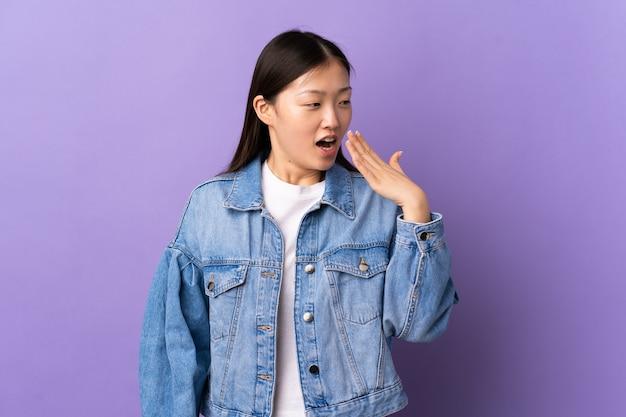 Jeune fille chinoise sur mur violet isolé le bâillement et couvrant la bouche grande ouverte avec la main