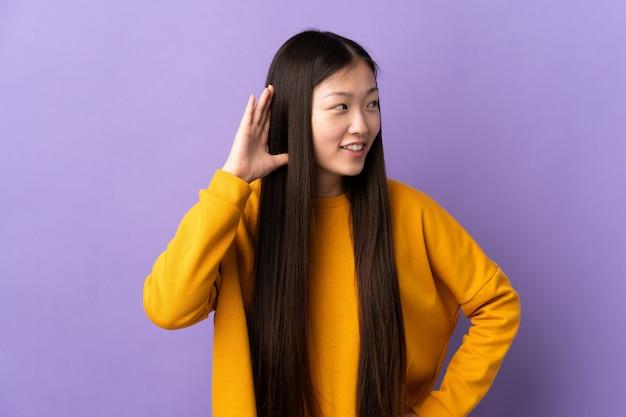 Jeune fille chinoise sur mur violet isolé écouter quelque chose en mettant la main sur l'oreille