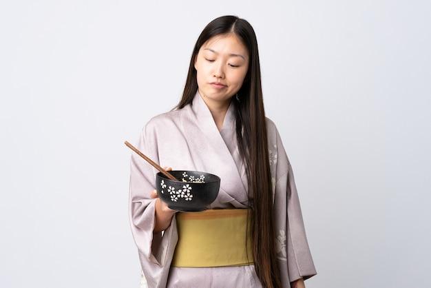 Jeune fille chinoise portant un kimono sur blanc avec une expression triste tout en tenant un bol de nouilles avec des baguettes