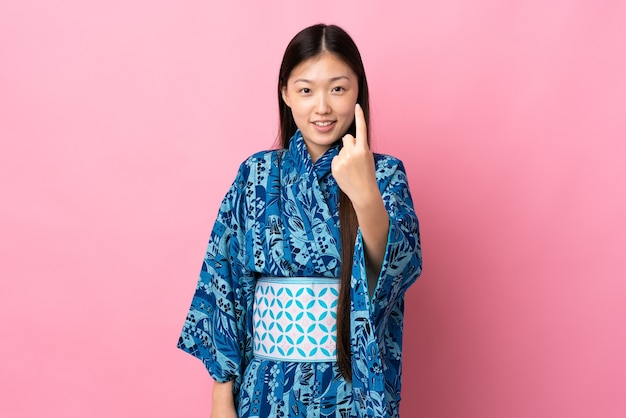 Jeune fille chinoise portant un kimono faisant le geste à venir