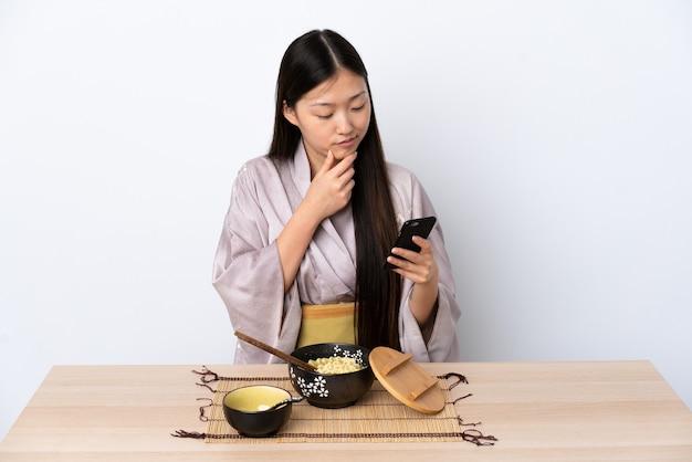 Jeune fille chinoise portant un kimono et manger des nouilles en pensant et en envoyant un message
