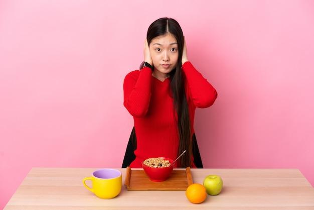Jeune fille chinoise prenant son petit déjeuner dans une table frustrée et couvrant les oreilles