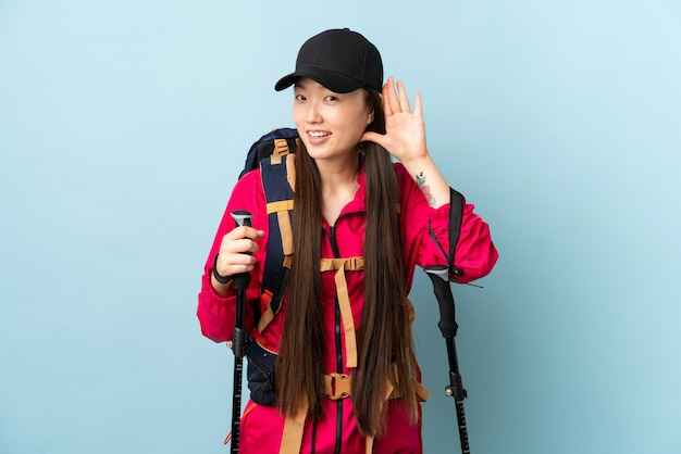Jeune fille chinoise avec sac à dos et bâtons de randonnée sur le mur bleu isolé écouter quelque chose en mettant la main sur l'oreille