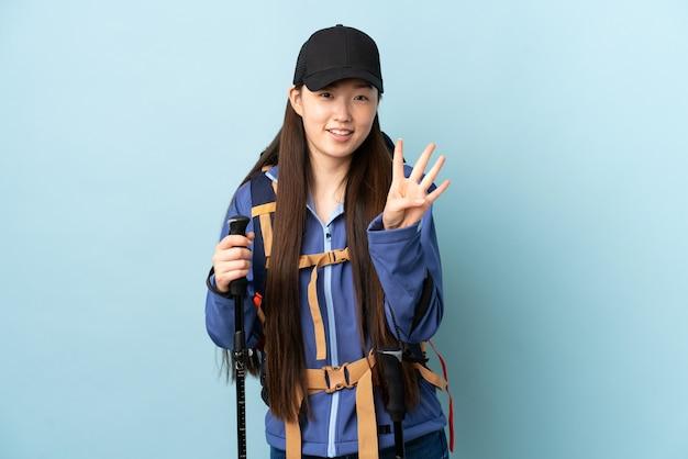 Jeune fille chinoise avec sac à dos et bâtons de randonnée sur le mur bleu isolé heureux et en comptant quatre avec les doigts