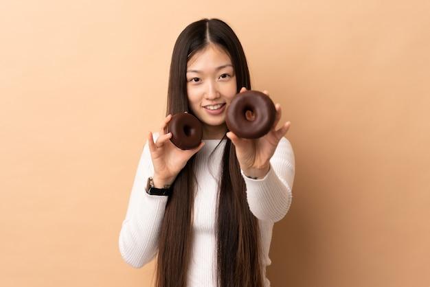 Jeune fille chinoise sur la tenue de beignets avec une expression heureuse