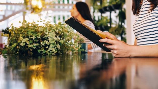 La jeune fille choisissant le menu au bar. jeune femme lisant le menu assis au café