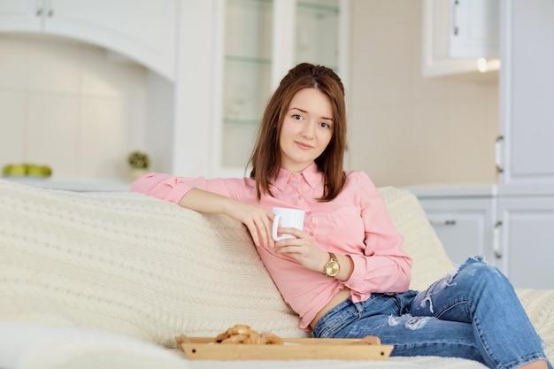 Une jeune fille avec une chope de boisson chaude est assise dans une pièce bien éclairée.