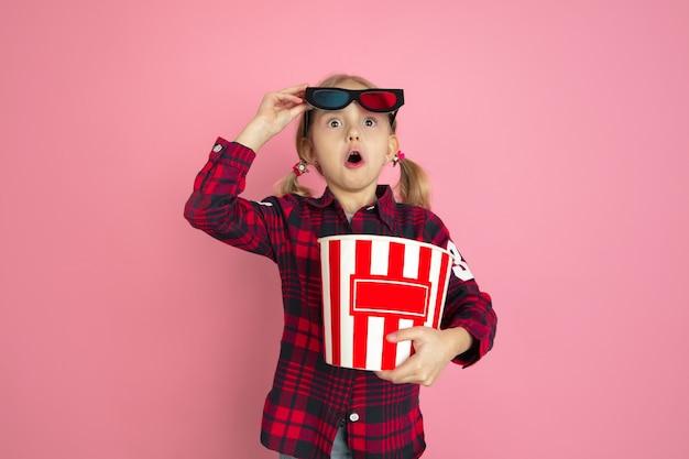 Jeune fille choquée et étonnée avec du pop-corn et des lunettes 3d sur un mur rose
