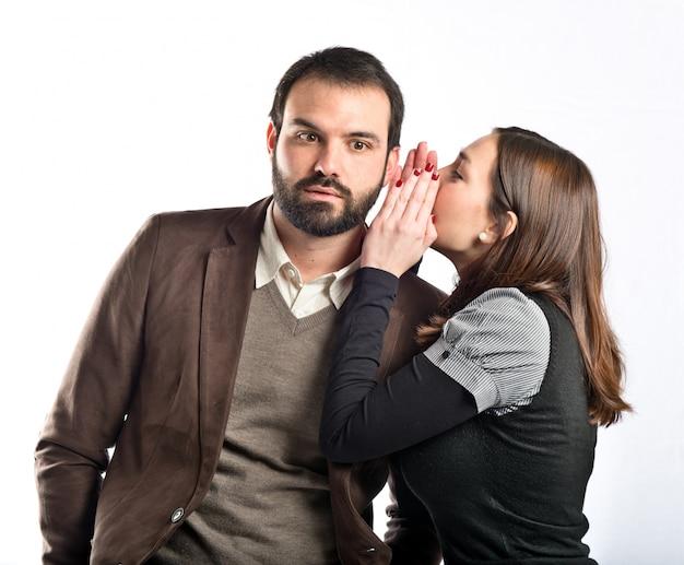 Jeune fille chuchotant à son petit ami sur fond blanc
