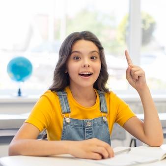 Jeune fille en classe ayant une idée
