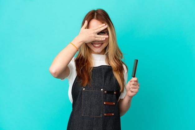 Jeune fille de coiffeur sur fond bleu isolé couvrant les yeux par les mains et souriant
