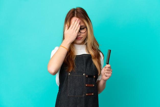 Jeune fille de coiffeur sur fond bleu isolé couvrant les yeux par les mains