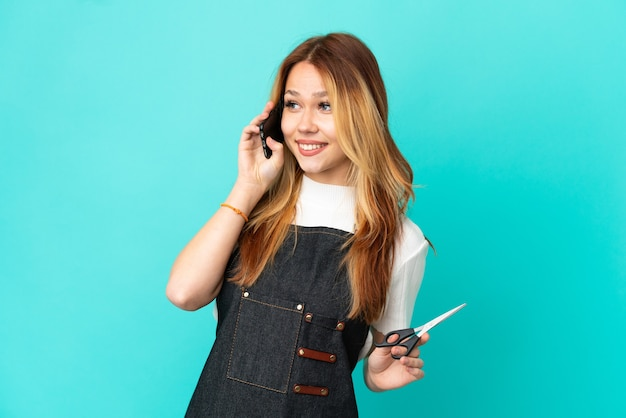 Jeune fille de coiffeur sur fond bleu isolé en gardant une conversation avec le téléphone portable avec quelqu'un
