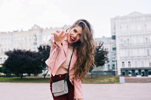 Jeune fille avec une coiffure longue s'amusant en ville. elle a un pantalon vineux, une veste rose, se penche vers la caméra.