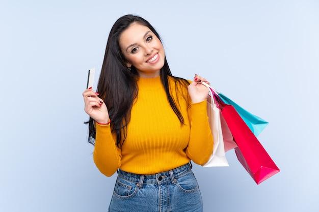 Jeune fille colombienne sur mur bleu tenant des sacs à provisions et une carte de crédit