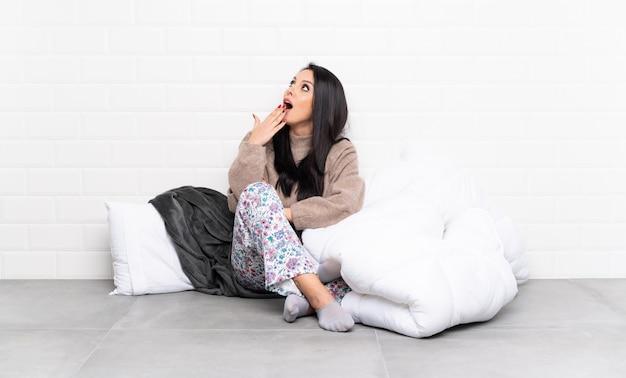 Jeune fille colombienne en pyjama à l'intérieur bâiller et cing bouche grande ouverte avec la main