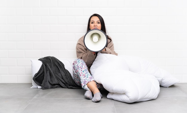 Jeune fille colombienne en pyjama à l'intérieur en criant à travers un mégaphone