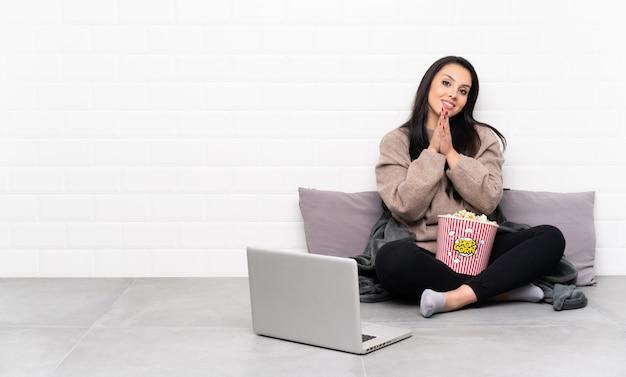 Jeune fille colombienne tenant un bol de pop-corn et montrant un film dans un ordinateur portable applaudissant après présentation lors d'une conférence