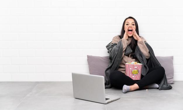 Jeune fille colombienne tenant un bol de pop-corn et montrant un film dans un ordinateur portable en criant et en annonçant quelque chose
