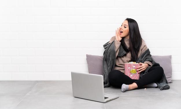 Jeune fille colombienne tenant un bol de pop-corn et montrant un film dans un ordinateur portable criant avec la bouche grande ouverte sur le côté