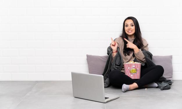 Jeune fille colombienne tenant un bol de pop-corn et montrant un film dans un ordinateur portable effrayé et pointant vers le côté